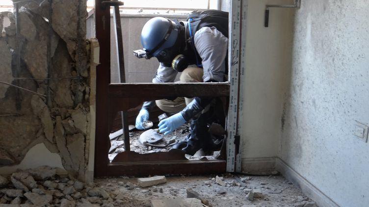 Un enquêteur de l'ONU collecte des données pour établir si le régime syrien a utilisé des armes chimiques contre la population, le 29 août 2013 à Damas (Syrie). (AMMAR AL-ARBINI / AFP)