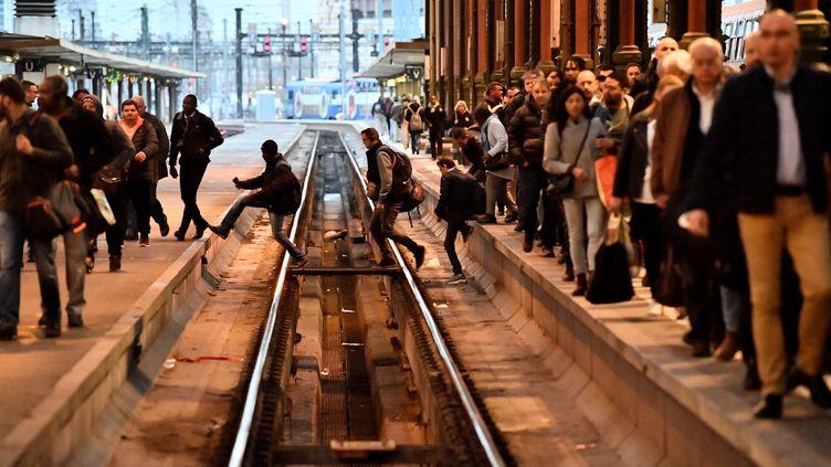 Des voyageurs traversent les voies de la gare de Lyon, à Paris, le 3 avril2018. (CHRISTOPHE SIMON / AFP)