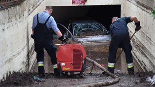 Des habitants nettoient l'entrée d'un parking souterrain àMandelieu-la-Napoule (Alpes-Maritimes), après les orages meurtriers, le 5 octobre 2015. (ANNE-CHRISTINE POUJOULAT / AFP)