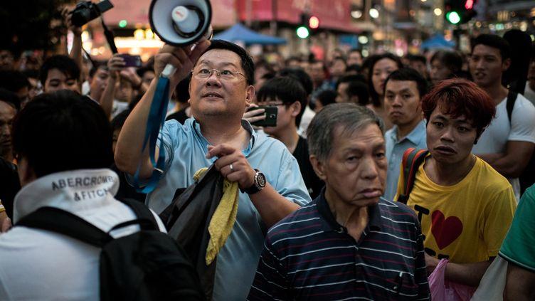 Une avec un mégaphone demande la dispersion de s manifestants pro-démocratie dans un quartierde Hong Kong, le 3 octobre 2014 (ALEX OGLE / AFP)