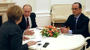 Le président français François Hollande échange avec son homologue russe Vladimir Poutine et la chancelière allemande Angela Merkel, lors d'une réunion consacrée à la crise en Ukraine, à Moscou (Russie), le 6 février 2015. (MAXIM ZMEYEV / AFP)