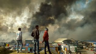 """Des migrants observentde loin une partie de la """"jungle"""" en flamme, Calais (Pas-de-Calais), le 26 octobre 2016 (PHILIPPE HUGUEN / AFP)"""