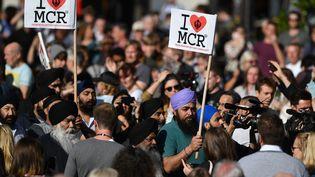 """Des membres de la communauté sikh manifestent leur amour de leur ville avec des pancartes """"I love MCR"""", le 23 mai 2017, à Manchester (Royaume-Uni), au lendemain d'un attentat meurtrier à la sortie d'un concert. (BEN STANSALL / AFP)"""