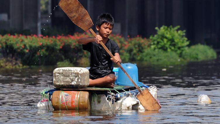Un enfant thaïlandais rame sur un radeau de fortune dans Bangkok inondée, lundi 24 octobre 2011. (PORNCHAI KITTIWONGSAKUL / AFP)
