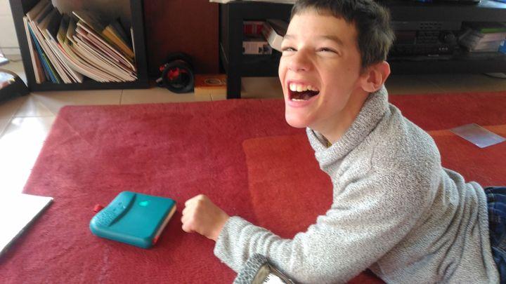 Antoine, 14 ans,est né avec une paralysie cérébrale. Il ne parle pas et n'a pas l'usage de ses mains. Dans sa maison à Meylan, Isère, le 25 mars 2020. (SERVANE HUGUES)