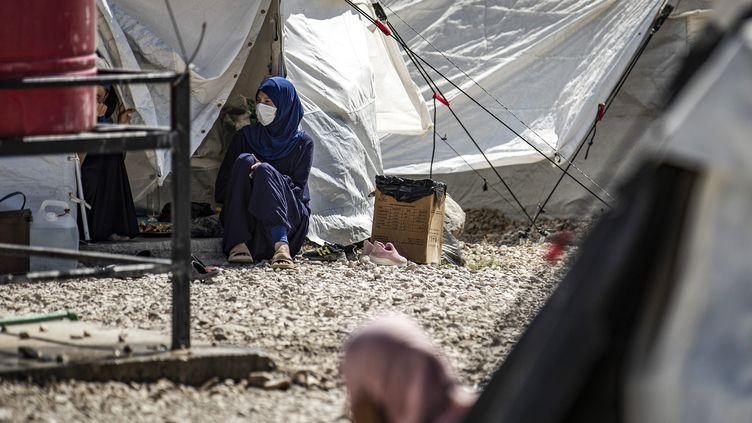 Une femme assise à l'extérieur d'une tente dans le Camp Roj en Syrie (photo d'illustration) (DELIL SOULEIMAN / AFP)