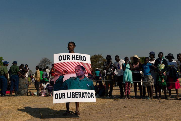 """Une jeune Zimbabwéenne tient une pancarte en hommage à Robert Mugabe, """"notre héros, notre libérateur"""", mortdans un luxueux hôpital de Singapour où il avait l'habitude de se faire soigner (photo du 16 septembre 2019). (JEKESAI NJIKIZANA / AFP)"""