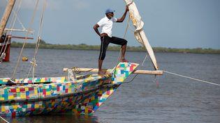 """Un marin du """"Flipflopi"""" se tient à la proue de ce bateau presqu'entièrement réalisé en plastique recyclé, lors de son lancement sur l'île de Lamu en septembre 2018. (BAZ RATNER / X02483)"""
