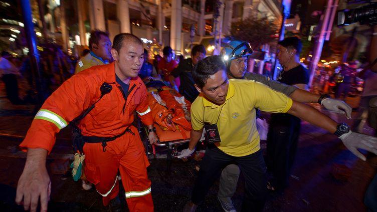 Les premiers sauveteurs transportent une blessé après l'explosion d'une bombe à Bangkok le 17 août 2015. (PORNCHAI KITTIWONGSAKUL / AFP)
