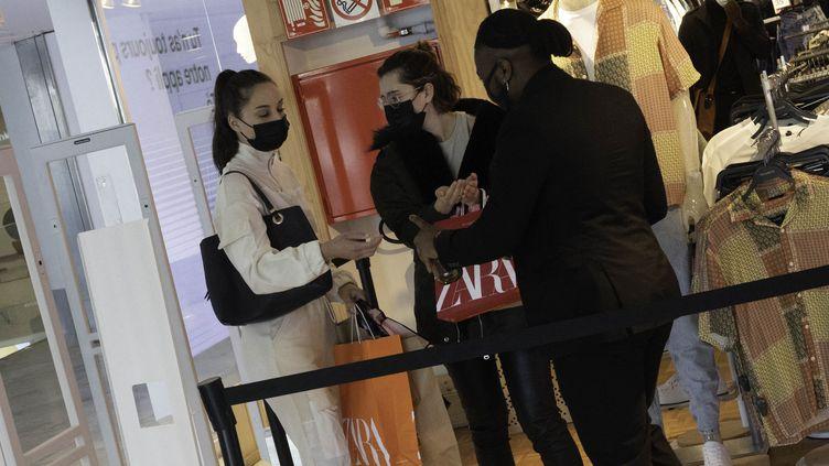 Des clientes reçoivent une dose de gel hydroalcoolique dans un magasin parisien, le 19 mai 2021. (ESTELLE RUIZ / HANS LUCAS / AFP)
