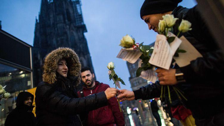 Un membre d'une association germano-tunisienne distribue des fleursdevant la gare centrale de Cologne (Allemagne), le 7 janvier 2016, alors que des dizaines d'agressions sexuelles y ont été commises contre des femmes durant la nuit du Nouvel An. (MAJA HITIJ / DPA / AFP)