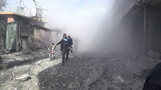 Des civils fuient le lieu d'une explosion après une frappe aérienne de l'aviation du régime syrien dans la Ghouta orientale, une enclave rebelle de l'est de Damas, le 8 février 2018. (SAMIR TATIN / AFP)