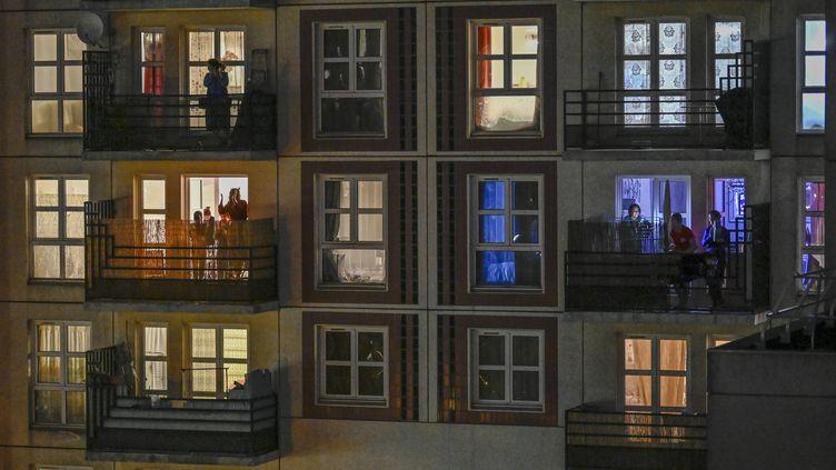 Des habitants d'une résidence de Montreuil (Seine-Saint-Denis) sur leur balcon, le 24 mars 2020. (REMI DECOSTER / HANS LUCAS / AFP)