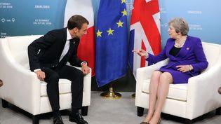 Theresa May, Premier ministre britannique (à gauche) et Emmanuel Macron, président de la République française (à droite), pendant le G7 à La Malbaie (Canada), le 8 juin 2018. (LUDOVIC MARIN / AFP)