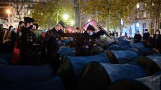 Des gendarmes tentent d'évacuer des tentes de migrants place de la République, à Paris, 23 novembre 2020. (MARTIN BUREAU / AFP)