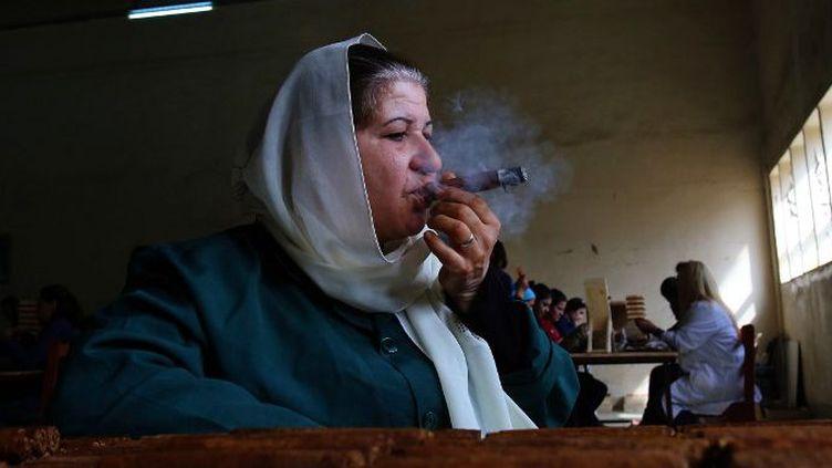 Une employé syrienne, Oum Ali, dans une usine qui produit ses premiers cigares fabriqués dans la province nord de Lattaquié, le 17 mars 2015. (AFP PHOTO / YOUSSEF KARWASHAN)