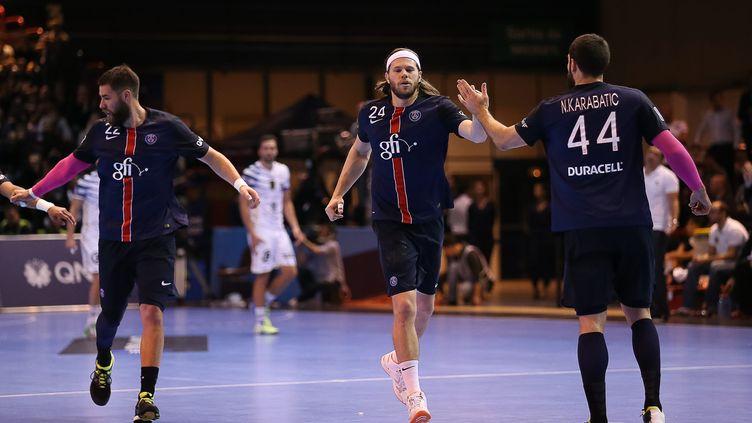 Mikkel Hansen (au centre), ici félicité par son coéquipier du PSG, Nikola Karabatic. (ANTHONY MASSARDI / MAXPPP)