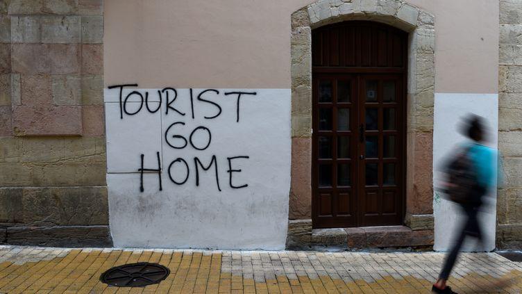 """Un graffiti """"Touristes, rentrez chez vous"""" dans le centre-ville d'Oviedo (province des Asturies, nord de l'Espagne), le 7 août 2017. (ELOY ALONSO / AFP)"""