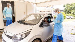 Des employés de l'institut Pasteur de Guyane réalisent un test de dépistage du Covid-19 sur un automobiliste le 23 juin 2020. (JODY AMIET / AFP)