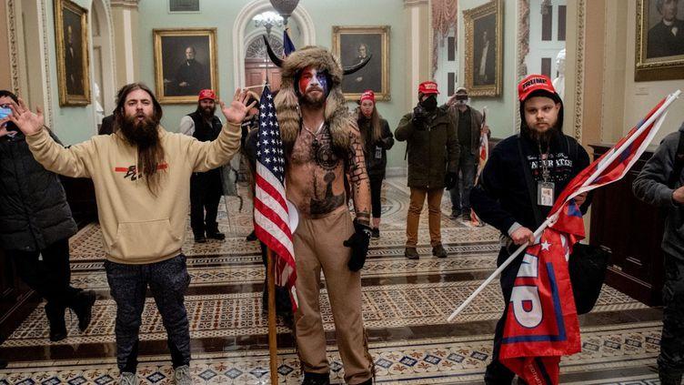 Des partisans du président américain Donald Trump, dont Jake Angeli, un partisan de QAnon, connu pour son visage peint et son chapeau à cornes, au Capitole, le 6 janvier 2021. (SAUL LOEB / AFP)