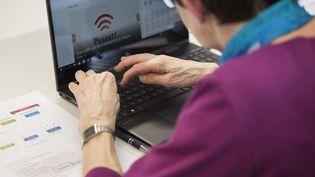 Une personne agée devant un ordinateur. (CHRISTIAN BEUTLER / MAXPPP)
