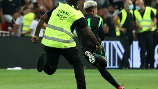 Un stadier poursuit un supporter entré sur le terrain, lors du match Nice-OM, le 22 août 2021. (VALERY HACHE / AFP)