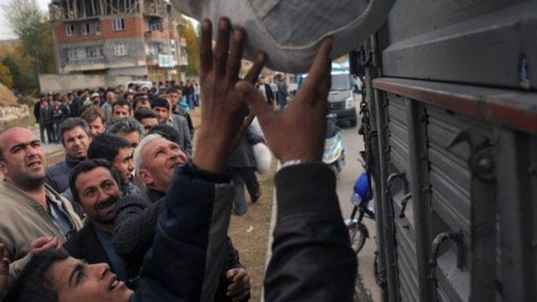 Des survivants sans abri du tremblement de terre reçoivent de l'aide à Ercis. (DIMITAR DILKOFF / AFP)