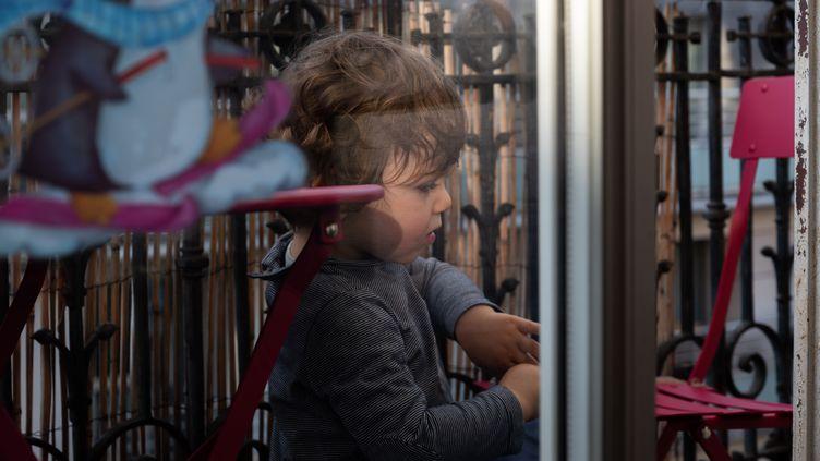 Un bébé joue sur un balcon à Paris, le 17 avril 2020. (RICCARDO MILANI / HANS LUCAS / AFP)