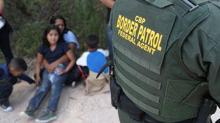 Des demandeurs d'asile venus d'Amérique centrale arrêtés par la police aux frontières américaine, le 12 juin 2018, près de McAllen au Texas (Etats-Unis). (JOHN MOORE / AFP)
