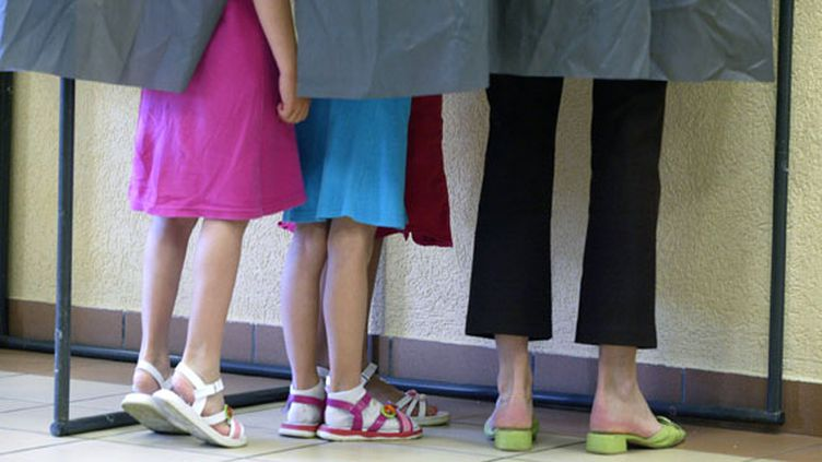 Des fillettes et leur mère dans un isoloir lors du premier tour de l'élection présidentielle, le 22 avril 2007 à Chanonat (Puy-de-Dôme). (THIERRY ZOCCOLAN / AFP)
