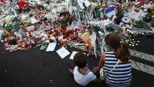 Des enfants devant l'hôtel Le Meridien, sur la promenade des Anglais, à Nice, deux jours après l'attentat 14-Juillet. (ANNE-CHRISTINE POUJOULAT / AFP)