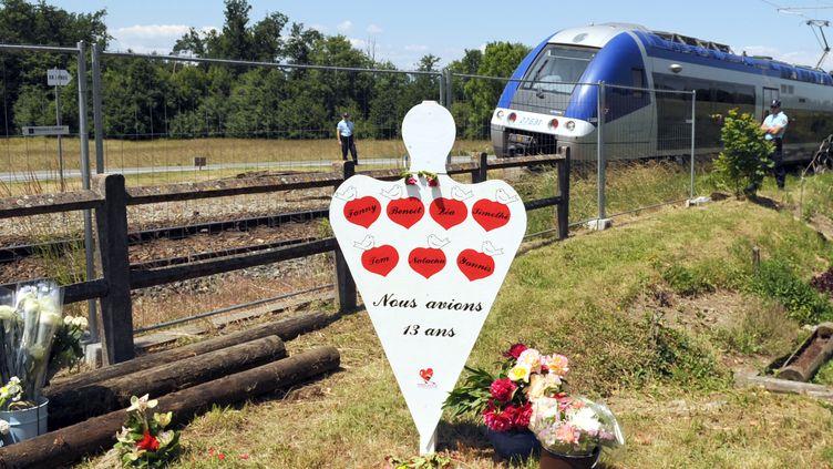 Un train TER marque l'arrêt le 2 juin 2009 à Allinges (Haute-Savoie) sur les lieux de l'accident, devant une silhouette portant les noms des sept collégiens morts dans le choc de leur car avec un train, en juin 2008. (JEAN-PIERRE CLATOT / AFP)