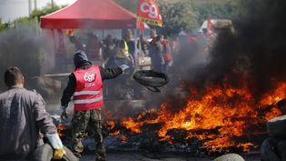 Un militant de la CGT alimente les flammes d'une barricade devant un dépôt de carburant, à Donges (Loire-Atlantique), le 19 mai 2016. (STEPHANE MAHE / REUTERS)