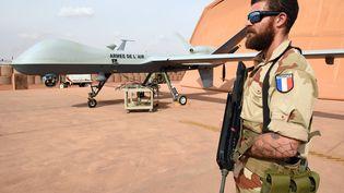 Un militaire français de l'opération Barkane se tient à côté d'un drone Reaper, le 14 mars 2016, à Niamey (Niger). (PASCAL GUYOT / AFP)