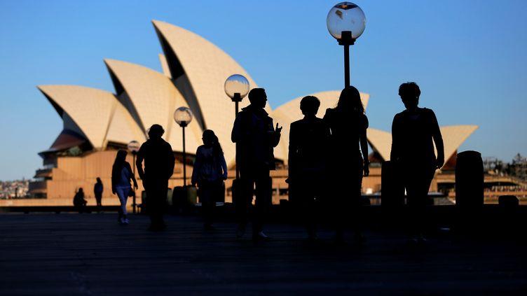 Des personnes marchent sur un quai à proximité de l'opéra de Sydey (Australie), le 2 novembre 2016. (STEVEN SAPHORE / REUTERS)