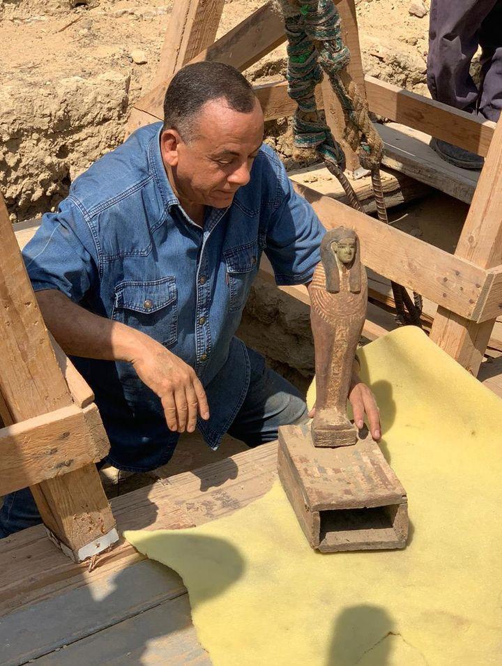 Mustafa Waziri, Secrétaire général du Conseil suprême des Antiquités, tenant une statue découverte dans la nécropole de Saqqara. (- / EGYPTIAN MINISTRY OF ANTIQUITIES)