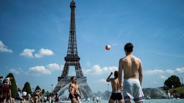 Des adolescents jouent au volley-balldans la fontaine de l'esplanade du Trocadéro à Paris le 25 juin 2019, un moismarqué par unecaniculeexceptionnelle. (KENZO TRIBOUILLARD / AFP)