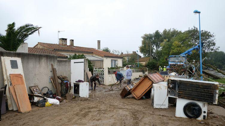 Des résidents nettoient les dégâts causés par les inondations àVillegailhenc (Aude), le 17 octobre 2018. (ERIC CABANIS / AFP)