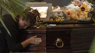 Une femme se recueille sur le cercueil d'une victime de l'effondrement du pont à Gênes, le 17 août 2018. (MARCO BERTORELLO / AFP)