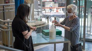 Deux femmes se lavent les mains au gel hydroalcoolique, à Montreal, au Canada, le 25 mai 2020. (SEBASTIEN ST-JEAN / AFP)