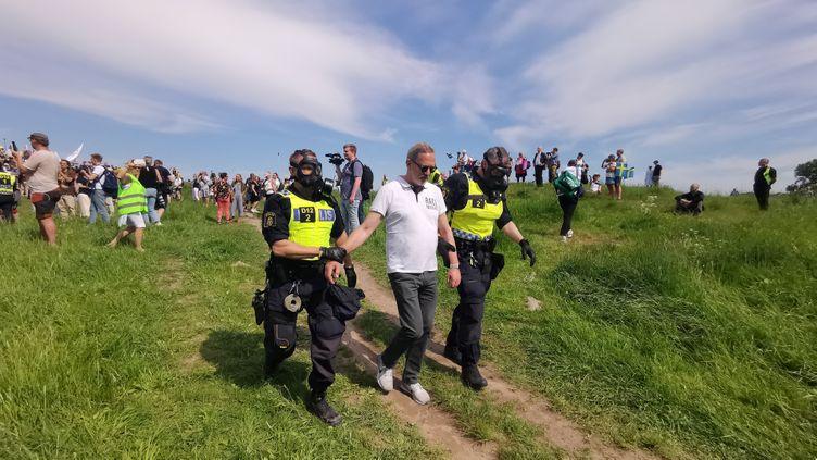 Des policiers suédois arrêtent un manifestant contre les restrictions sanitaires contre le Covid-19 à Stockholm le 6 juin 2021. (ATILA ALTUNTAS / ANADOLU AGENCY)