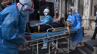 Un malade atteint du coronavirus emmené dans une ambulance, le 30 janvier 2020 à Wuhan (Chine). (HECTOR RETAMAL / AFP)
