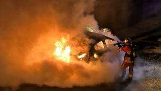 Un pompier lutte contre l'incendie d'une voiture à Marseille, le 26 décembre 2017. (GERARD BOTTINO / CROWDSPARK / AFP)