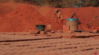 Un ouvrier sépare la terre crue et les roches à Elementerre, une entreprise spécialisée dans brique en terre compressée, le 10 mai 2021, Mbour, Sénégal. (ZOHRA BENSEMRA - REUTERS)