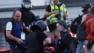 Un policier anti-émeute confisque la carte mémoire d'une photographe lors d'un rassemblement de partisans de l'opposition, à Minsk le 11 août 2020. (SERGEI GAPON / AFP)
