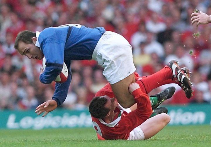 Le rugbyman français Richard Dourthe est plaqué par le gallois Rob Howley, lors du match amical opposant le Pays de Galles à la France, le 28 août 1999, au Millennium Stadium de Cardiff. (PATRICK KOVARIK / AFP)