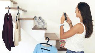 Une adolescente photographie des vêtements avec son téléphone dans le but de les vendre sur la plateforme Vinted, le 1er mai 2020. (PHILIPPE TURPIN / PHOTONONSTOP / AFP)