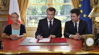 Emmanuel Macron signe le projet de loi de réforme de la SNCF, entouré de la ministre des transports,Elisabeth Borne, et du porte-parole du gouvernement,Benjamin Griveaux, le 27 juillet 2018, au palais de l'Elysée, à Paris. (JULIEN DE ROSA / AFP)