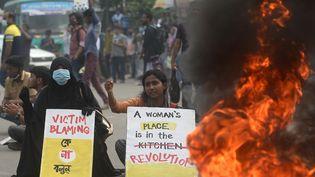 Des étudiantes tiennent des pancartes à côté d'un pneu en feu alors qu'elles bloquent une route lors d'une manifestation contre le viol et la torture d'une femme à Dhaka (Bangladesh) le 21 octobre 2020. (MUNIR UZ ZAMAN / AFP)