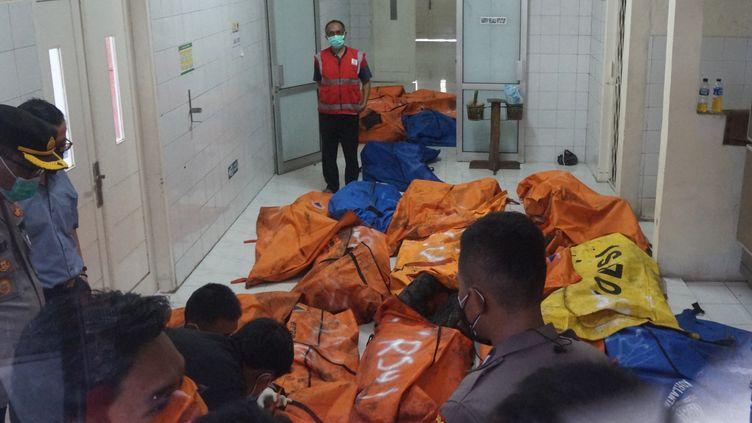 Des policiers et des personnels soignants stockent les corps des victimes de l'incendie survenu dans une prison de la région de Jakarta (Indonésie), le 8 septembre 2021. (FAJRIN RAHARJO / AFP)